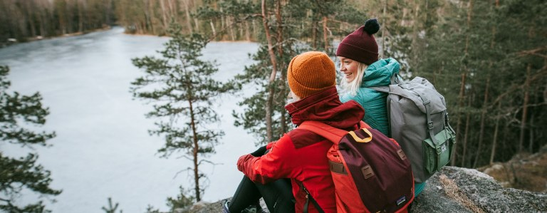 Two beanie-headed people sit on a rock and a forest lake is visible below.