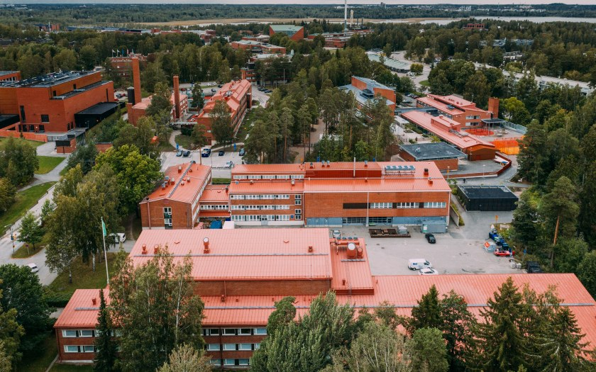 Areal image of red brick buildings surrounded by tall fir and birch trees.