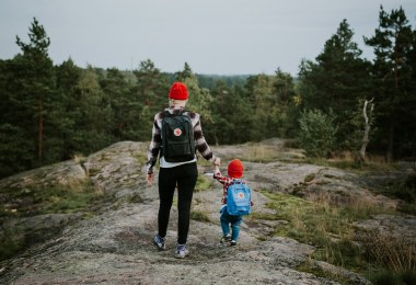 A woman and a boy are walking in forest and holding hands.