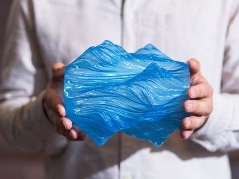A closeup of hands holding blue 3D printmaterial.
