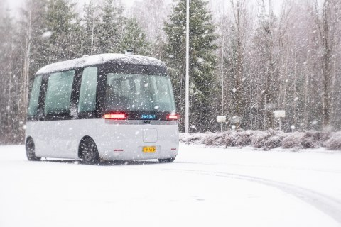 A shuttle bus driving in and leaving tracks in the snow with snow falling down.
